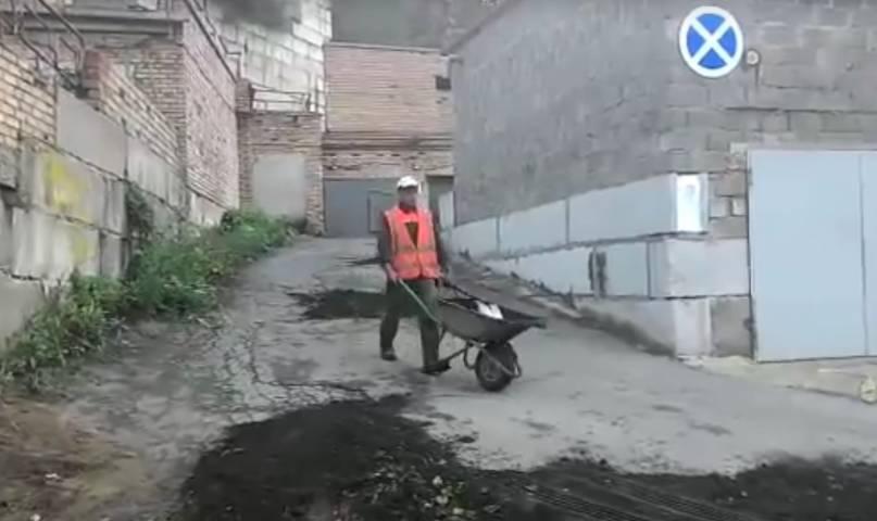 Рабочие во Владивостоке засыпают ямы землей с газона